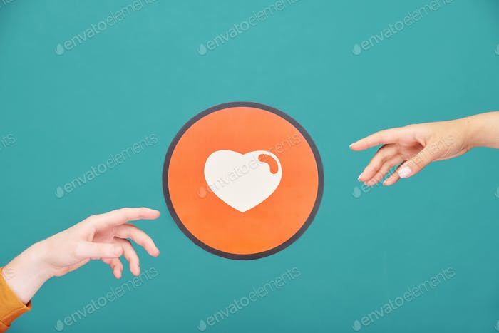 Hands of young man and woman reaching out for picture of heart in red circle