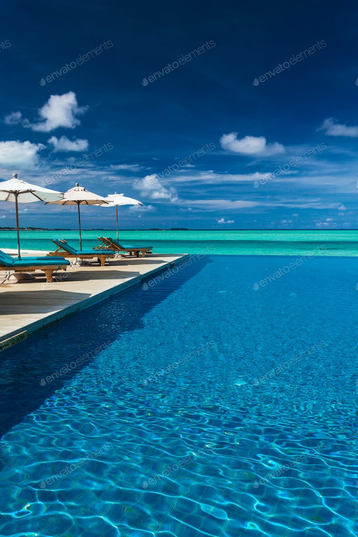 Infinity swimming pool on the beach of tropical island with whit