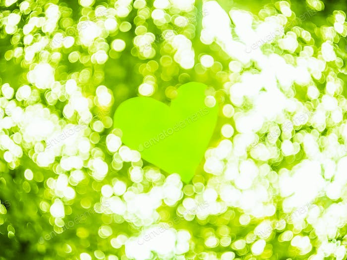 Green Heart On White And Green Colors Bokeh Abstract Light. Valentine's Day Background