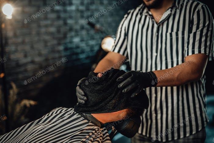 Мужское лицо высыхает с шляпой после бритья в парикмахерской