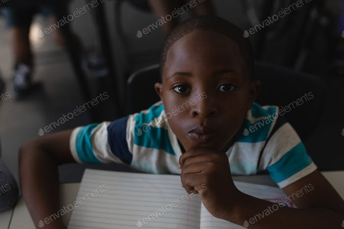 Schoolboy with hand on chin sitting at desk and looking at camera in classroom of elementary school