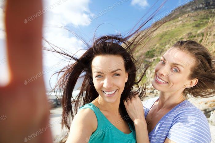Two smiling friends enjoying taking selfies