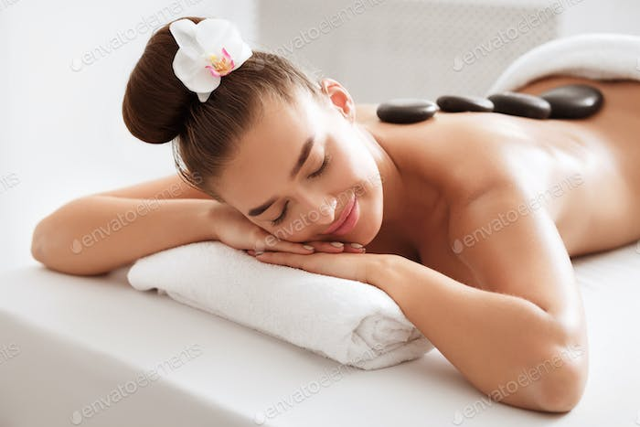 Relaxed woman enjoying hot stone massage at spa