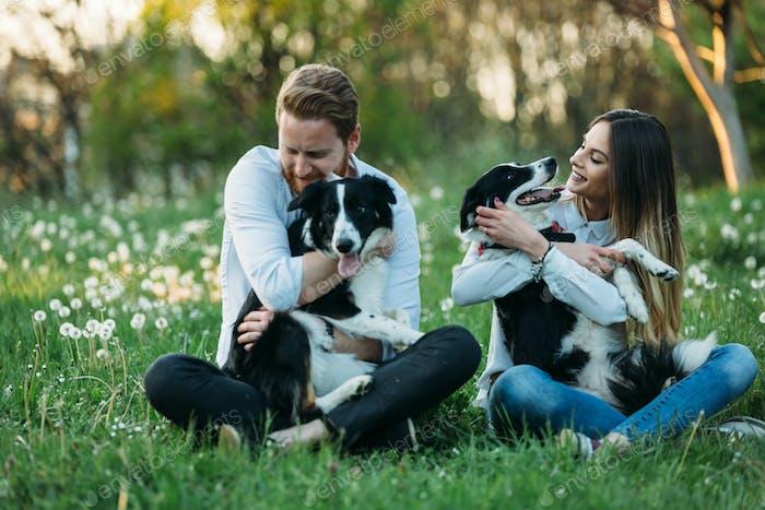 Schönes paar Kuscheln und Walking Hunde im Freien