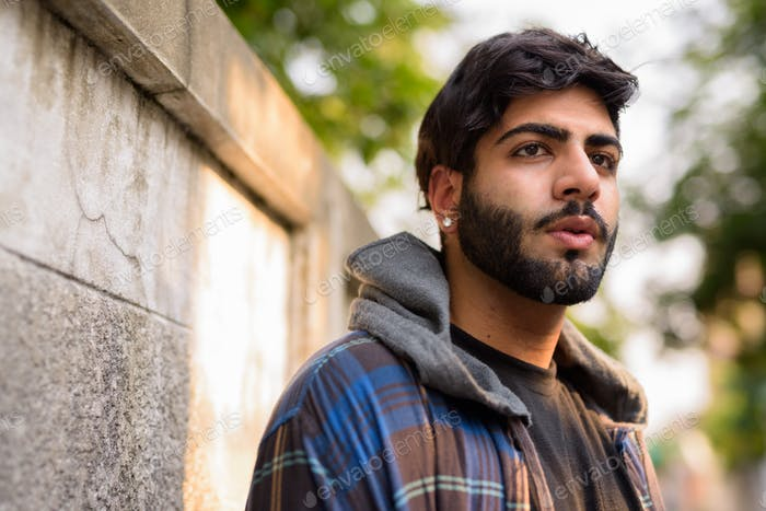 Face of young handsome bearded Indian hipster man thinking in the streets