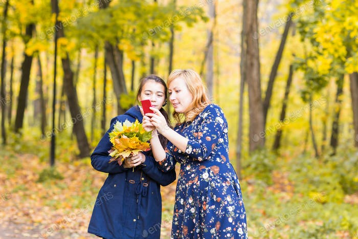 Mother showing her Teenage girl photos on mobile phone outdoor in autumn nature