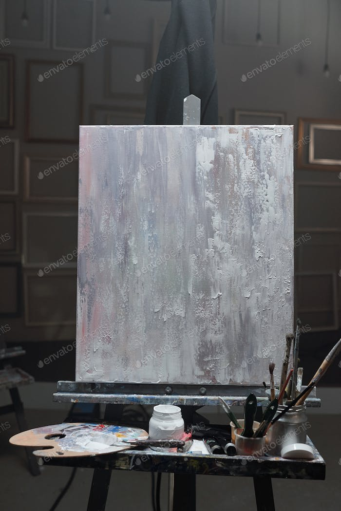 Easel with unfinished picture and set of stuff for professional painting