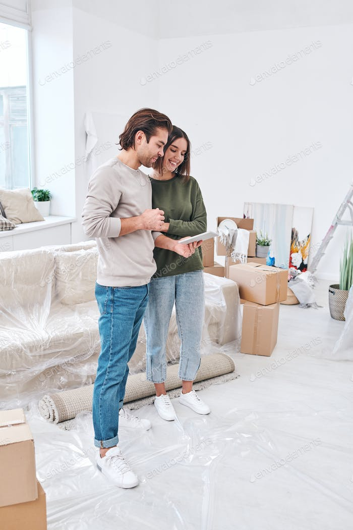 Happy young amorous settlers of new house or flat standing in living-room
