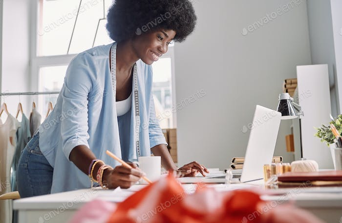 Beautiful young African woman sketching and smiling