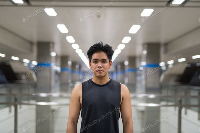 Young handsome Asian man at the subway station