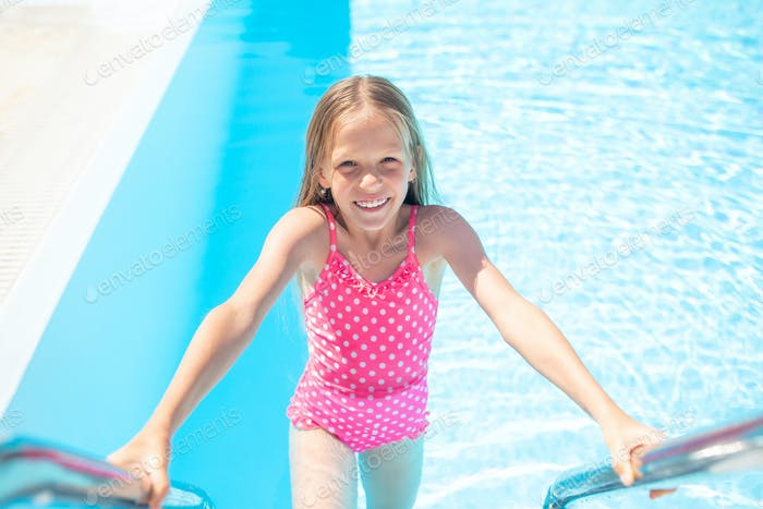Little adorable girl in outdoor swimming pool