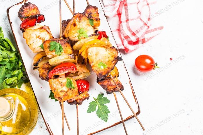 Chicken kebab on skewers on white