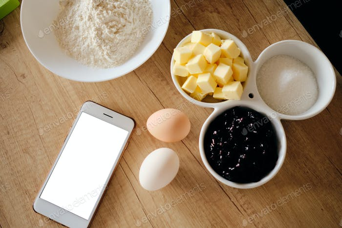 Ingredients for cake on table and smart phone with white screen
