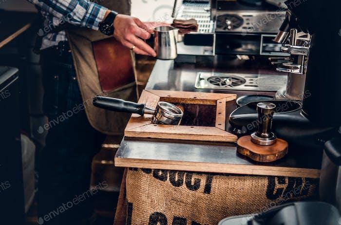 A man preparing cappuccino in a coffee machine.