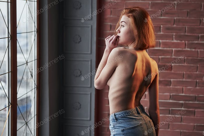 Desired look. Hot young blonde with bare chest and jeans stands against the window and brick wall
