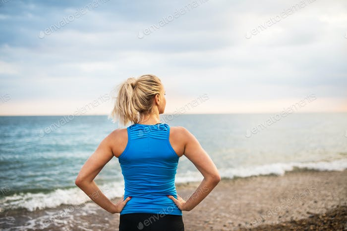 Rear view of young sporty woman runner in blue sportswear standing on the beach.