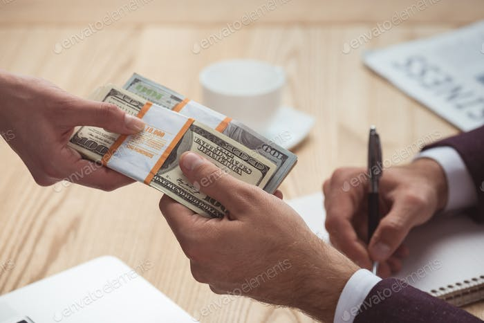 cropped view of businesspeople holding dollar banknotes, salary concept