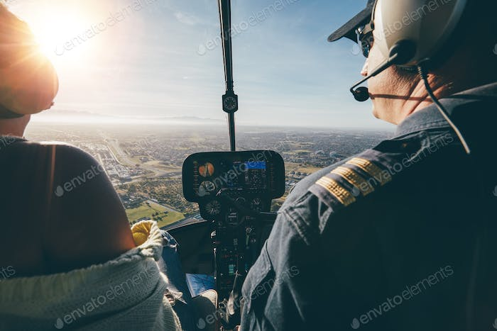 Two pilots flying a helicopter on sunny day