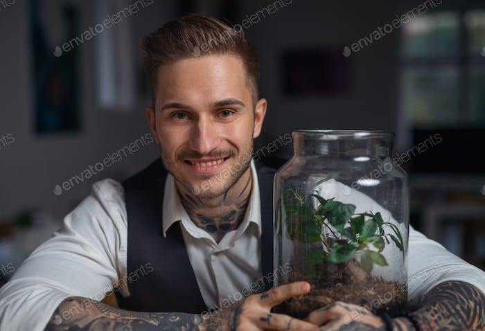A businessman with plant terrarium sitting at the desk indoors in office