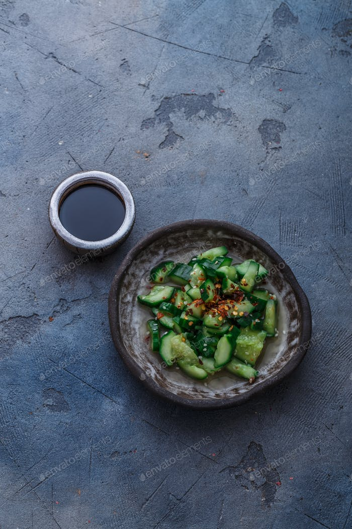 Chinese beaten cucumbers salad, top view, dark background, place for text