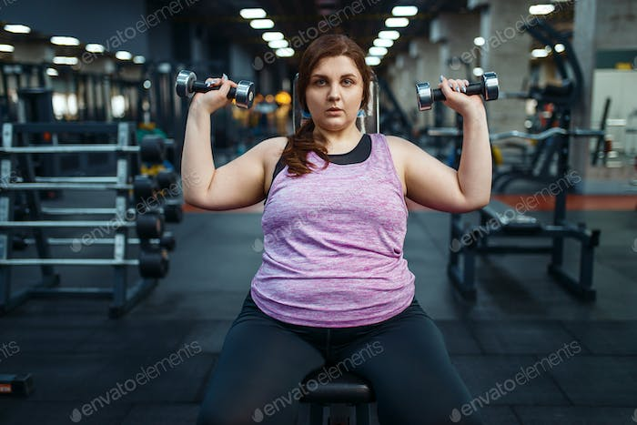 Overweight woman poses with dumbbells in gym