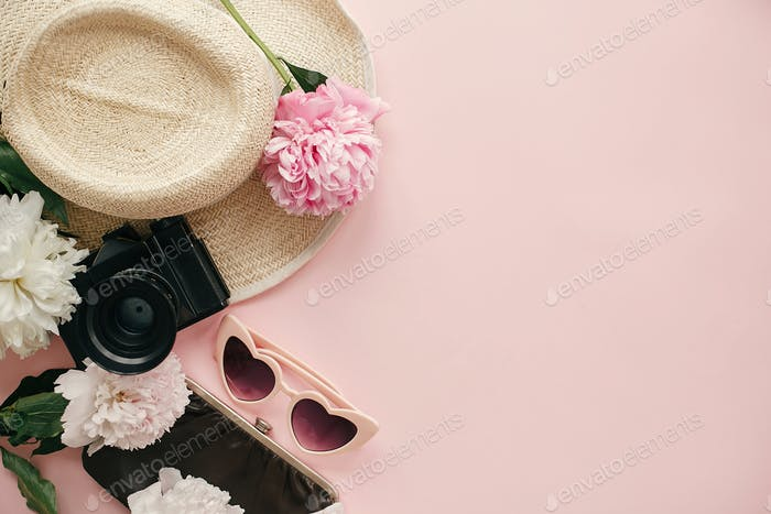 Stylish girly image of peonies, photo camera, retro sunglasses, hat, purse on pastel pink paper