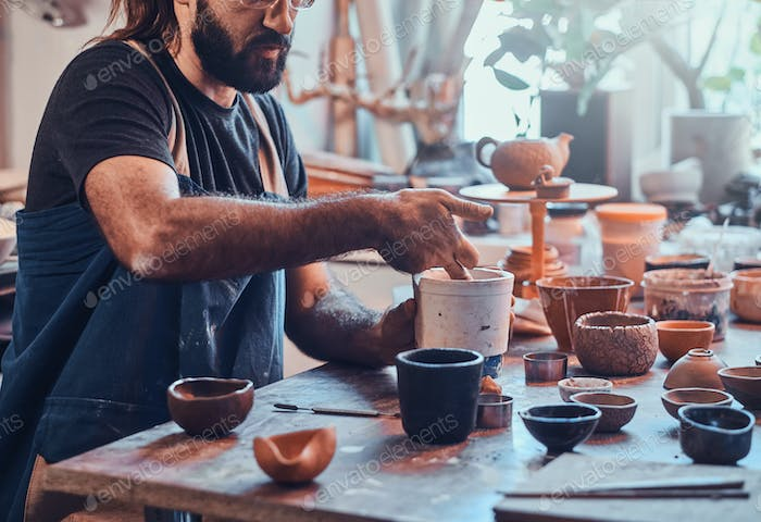 Man is putting colourful clay to his new handmade pot.