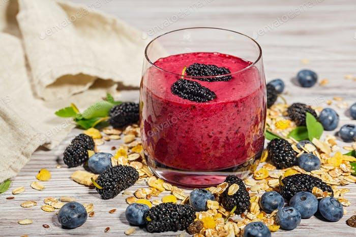 Glass of smoothies, muesli and fresh berries