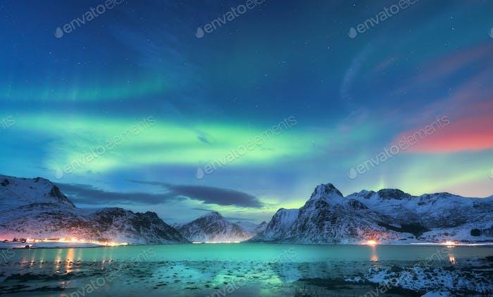 Aurora borealis über der Meeresküste, verschneite Berge und Stadt
