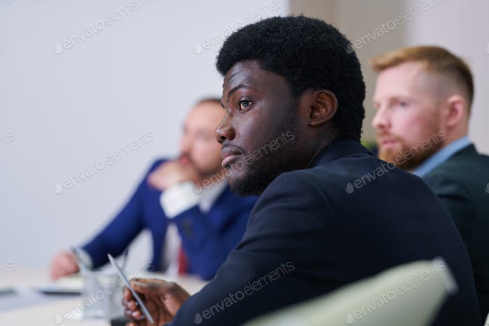 Serious young African businessman or student listening to speaker