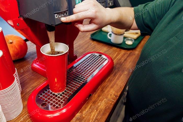 Stylish soda machine on wooden desk