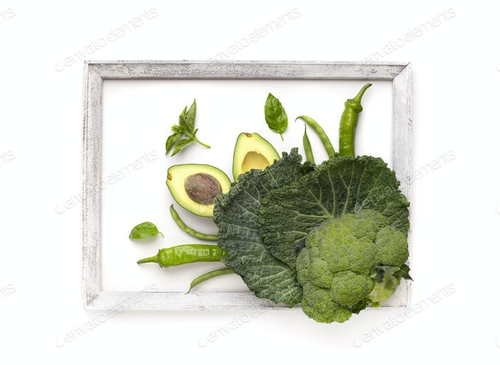 Green vegetables inside frame on white background