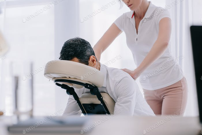 masseuse doing seated massage for businessman