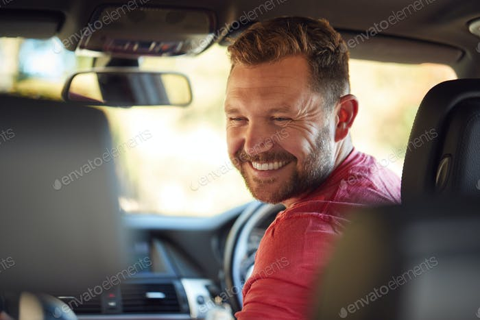 Father Turning Round To Talk To Children In Back Seat On Car Journey
