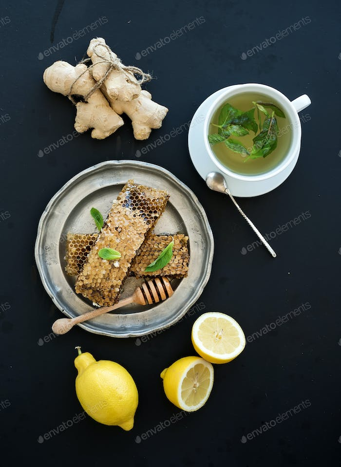 Cup of herbal tea with fresh mint, honey, lemon, ginger on grunge black  background