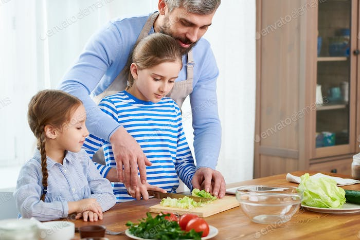 Loving Family Preparing Vegetable Salad