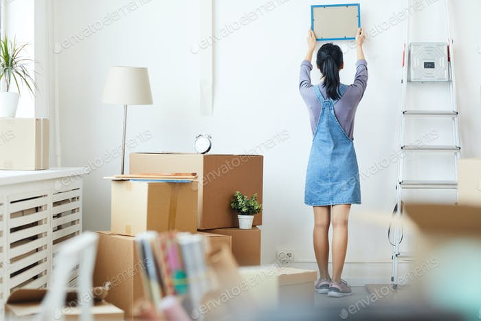 Young Woman Unpacking Boxes in New Home