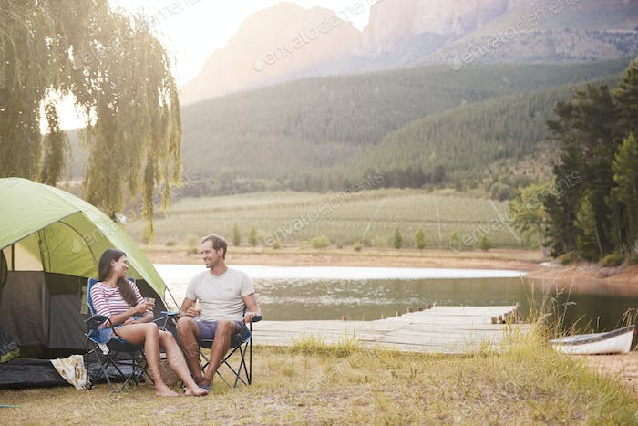 Couple Enjoying Camping Vacation By Lake Making A Toast