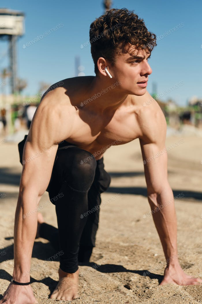 Young confident sporty man preparing running outdoor. Handsome guy training on city beach