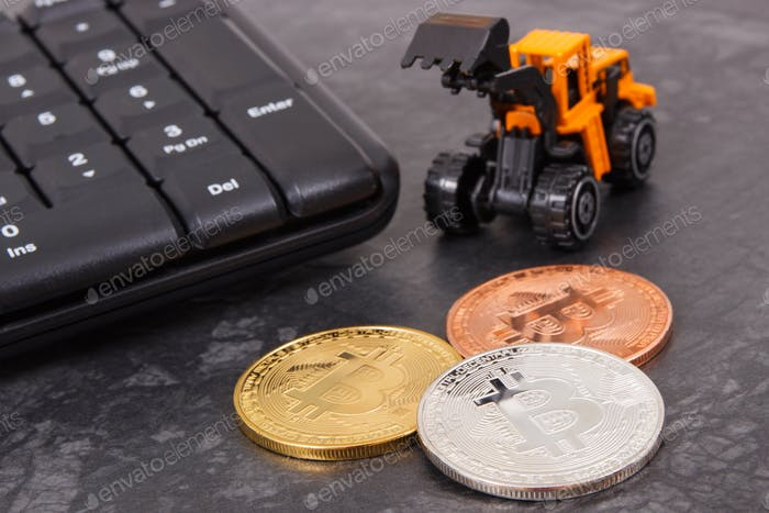 Bitcoins as symbol of electronic virtual money, miniature excavator and computer keyboard