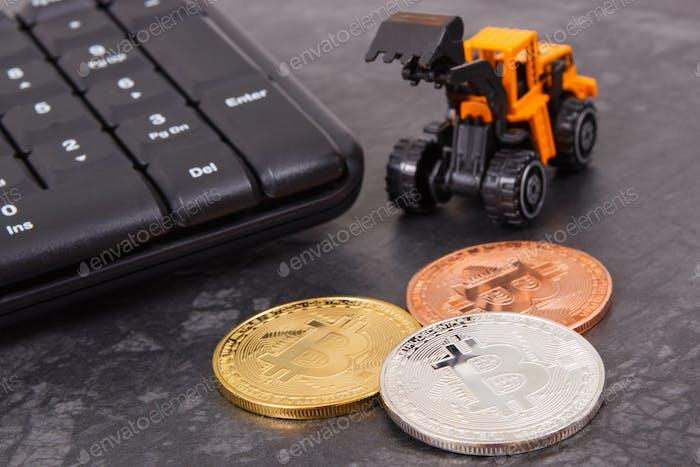 Bitcoins als Symbol für elektronisch isches virtuelles Geld, Miniaturbagger und Computertastatur