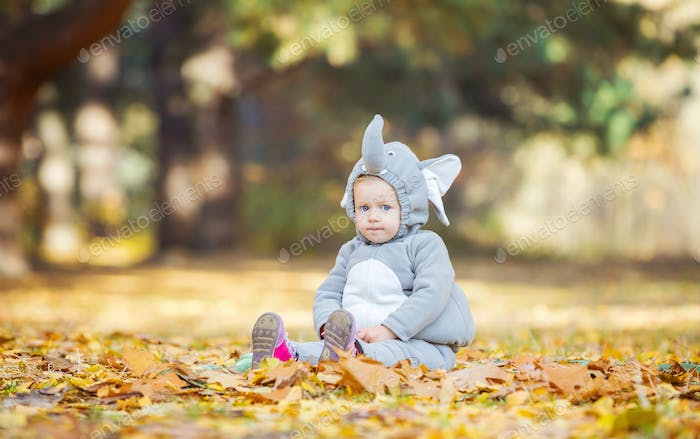 Little girl in elephant costume playing in autumn forest
