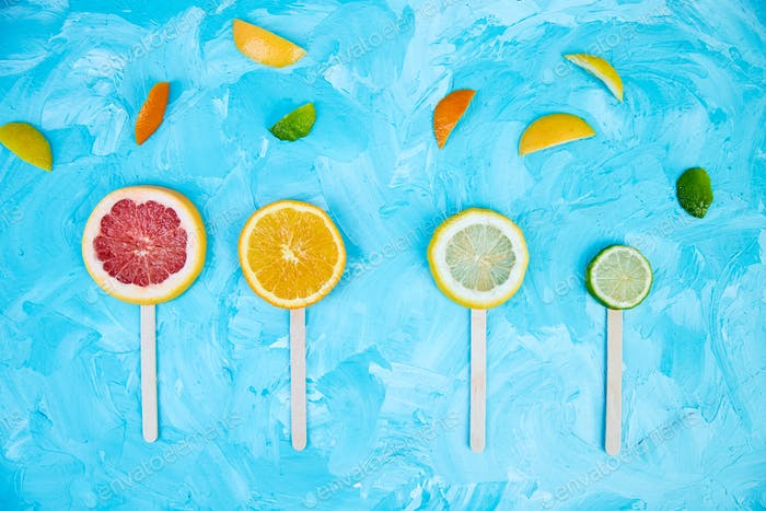 Citrus slice popsicles on a blue background.