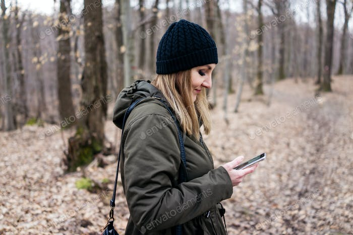 Woman using mobile smartphone outdoor in forest