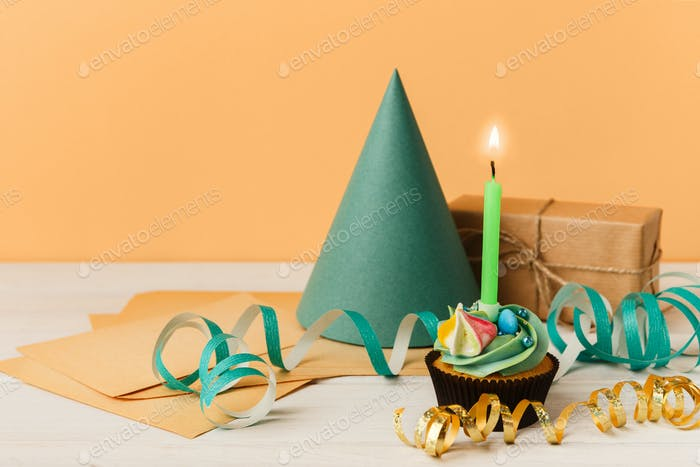 Delicious cupcake and gift on yellow background