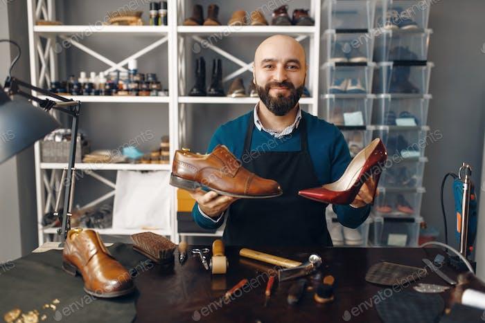 Bootmaker показывает отремонтированную обувь, ремонт обуви
