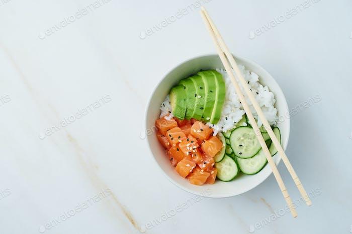 salmon poke bowl with fresh fish, rice, cucumber, avocado