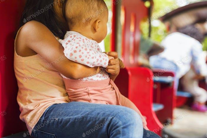 Girl (6-7) holding sister (6-11 months)