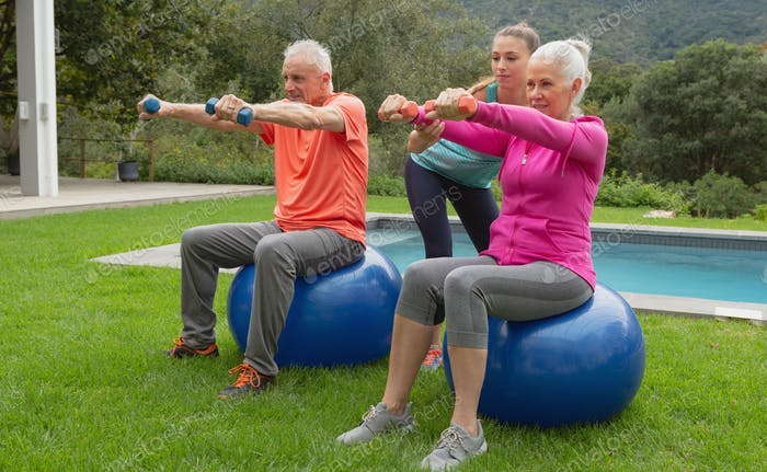 Caucasian female trainer assisting active senior Caucasian couple to exercise with dumbbells