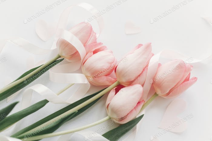 Pink tulips with ribbon and hearts on white background